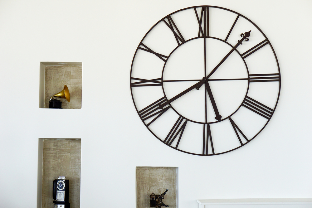 Clock hanging on the wall next to shelves