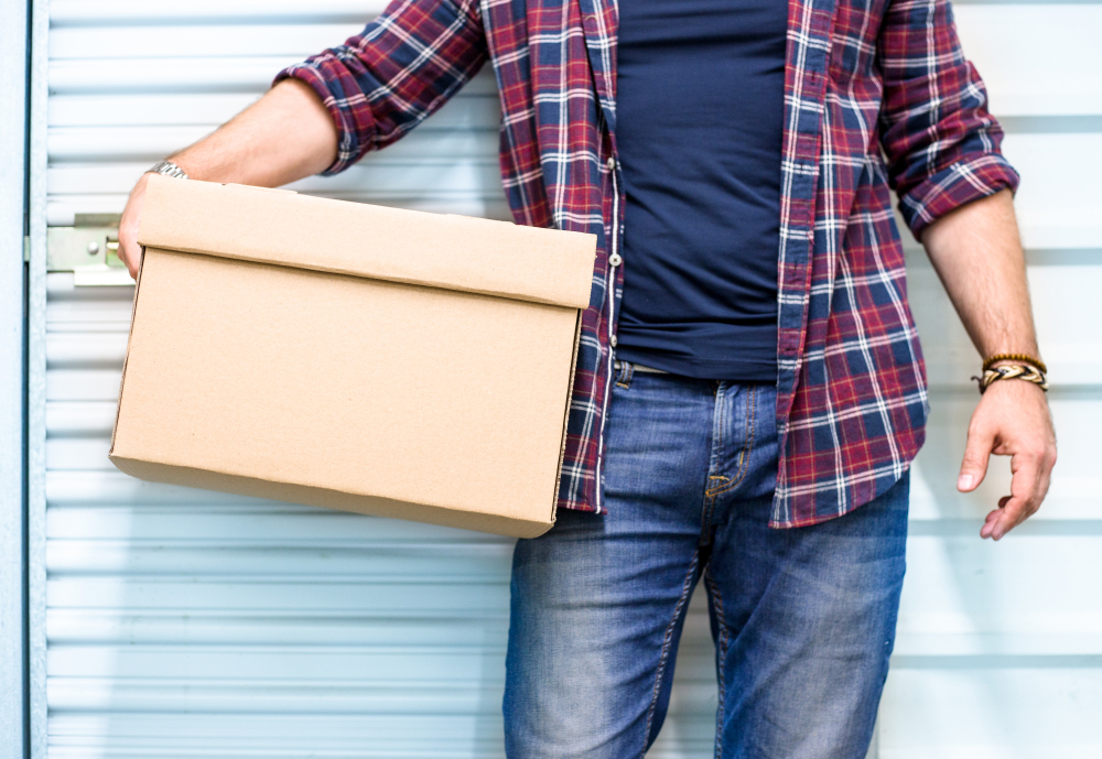 Man holding box in front of storage unit door