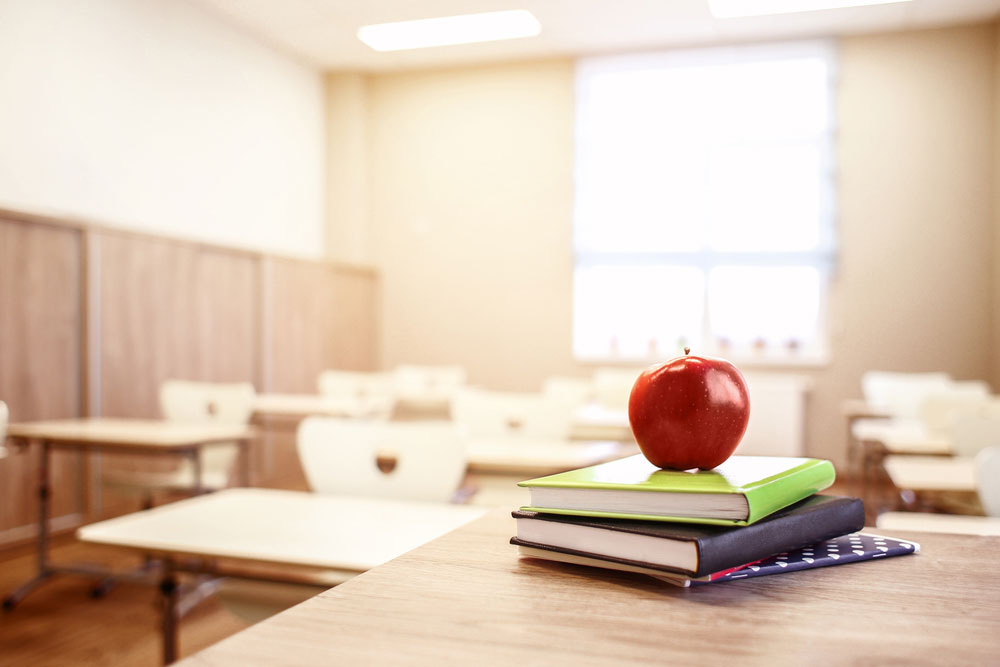 An apple placed on textbooks in an empty classroom