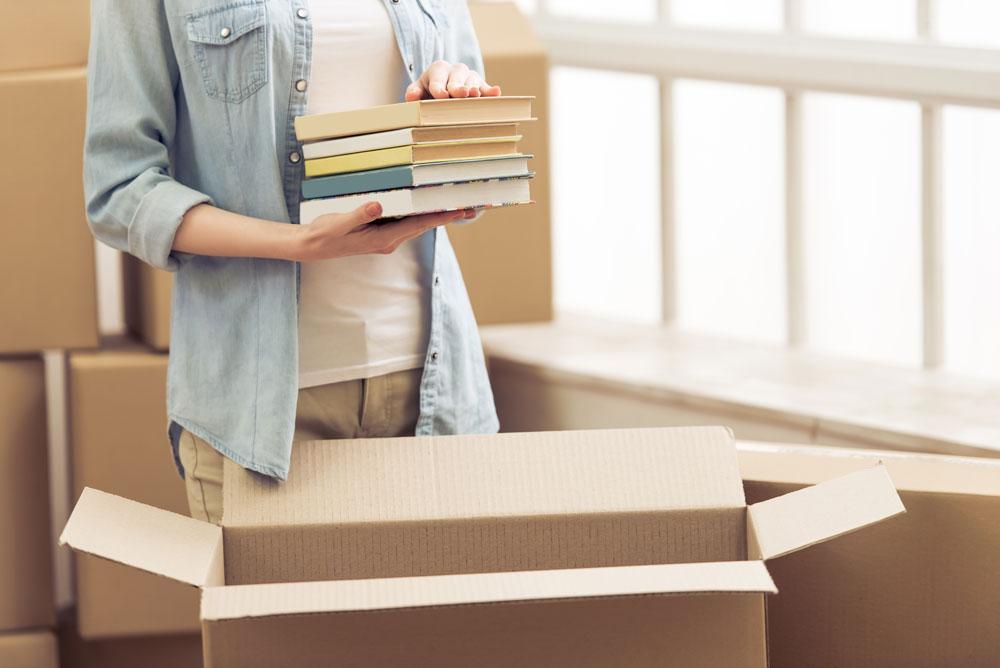 Woman putting books in a box