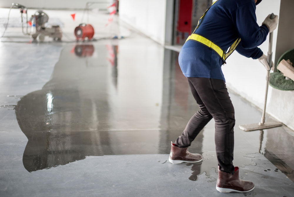 an unidentifiable person cleaning concrete floors