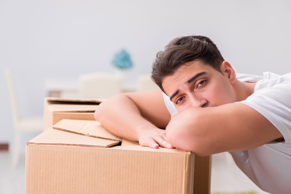 young man leaning over personal storage boxes looking defeated