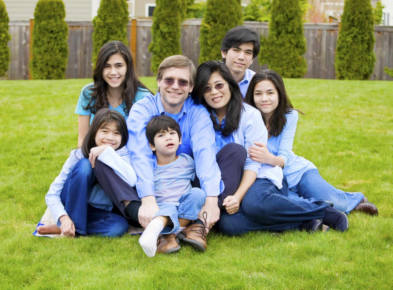 large family sitting on lawn needs storage solutions from Affordable Family Storage