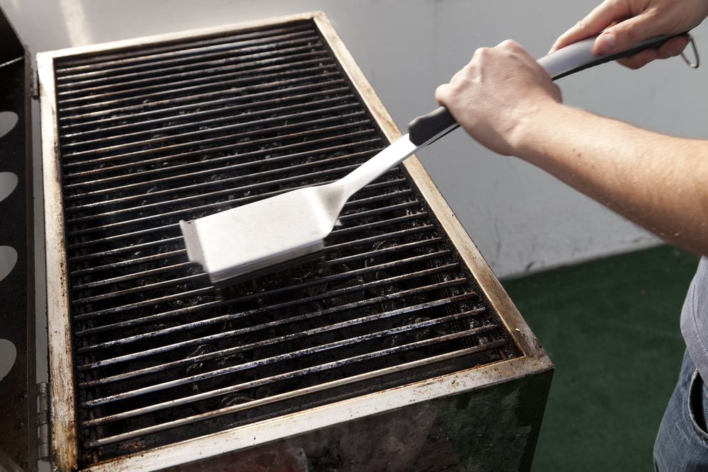 Person cleaning grill in preparation for placing in storage space