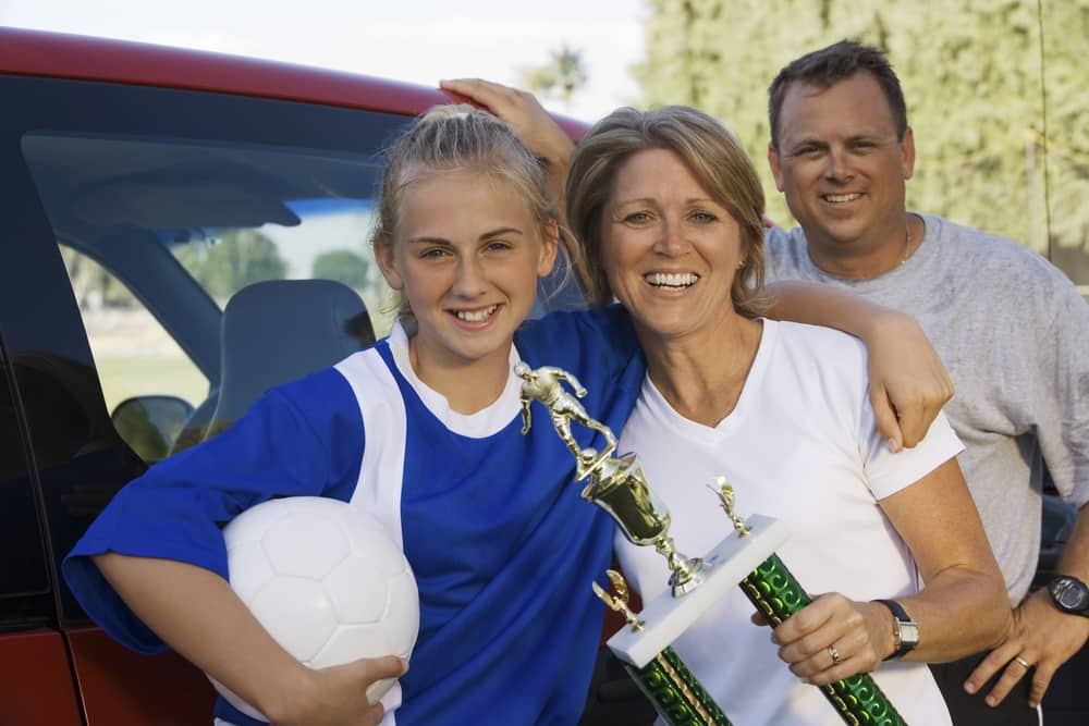 Parents and child posing with soccer ball and trophy