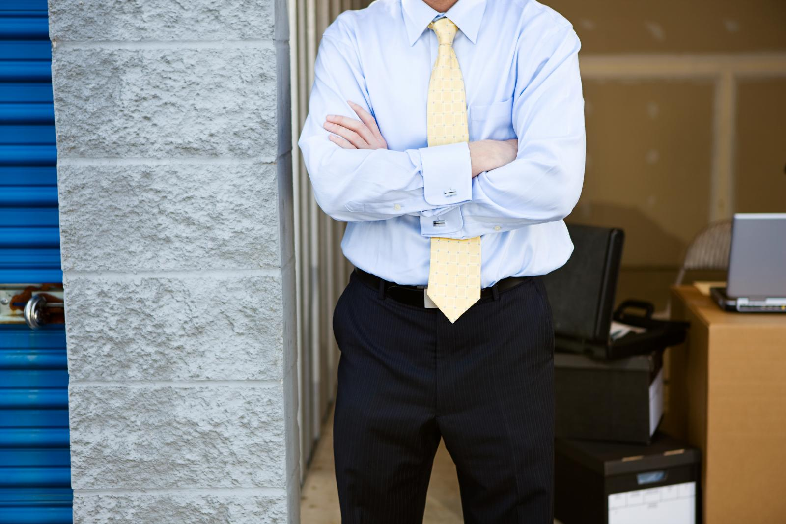 businessman stands outside one storage space of many