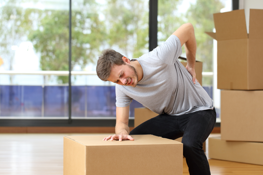 Man suffering back injury when moving boxes to storage rental
