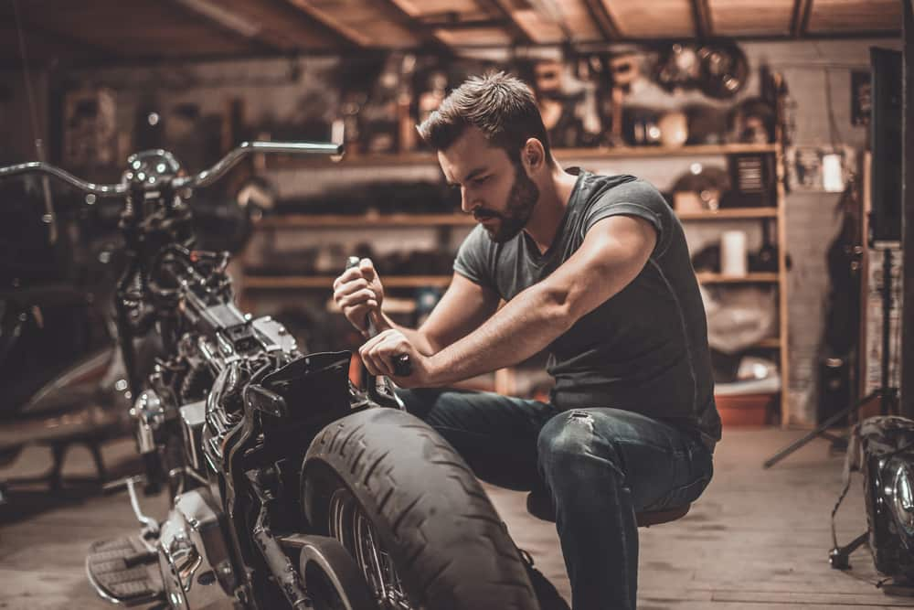 Man preparing motorcycle for a self storage unit.