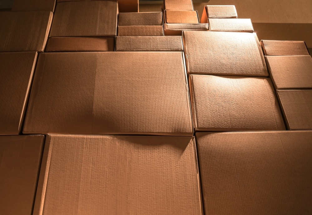 wall of stacked cardboard boxes in a storage unit