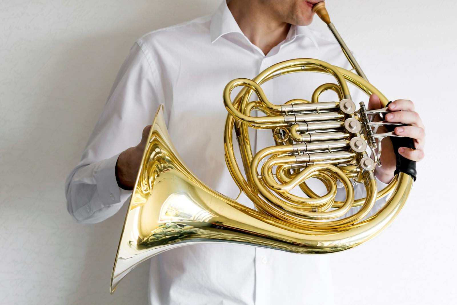 Man playing brass instrument before placing in storage unit.