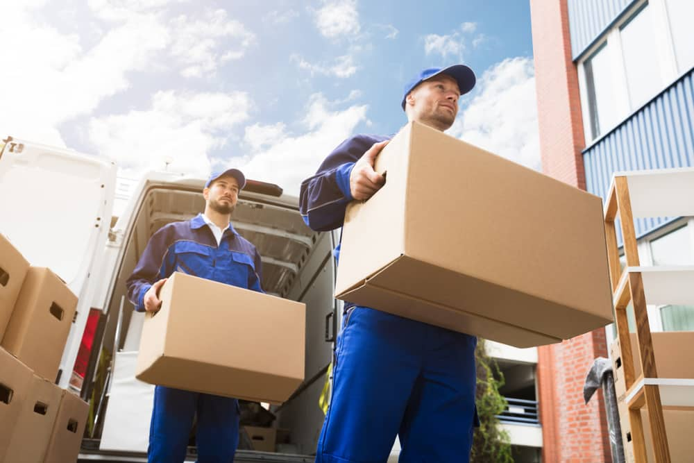 two men unloading boxes as if helping family unload storage