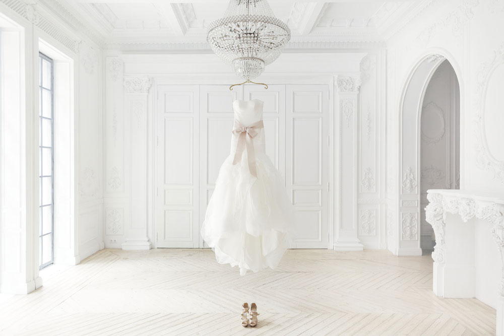 Wedding gown hanging from crystal chandelier in the middle of ornate room