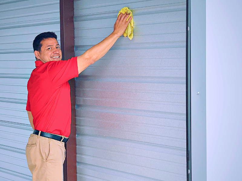 Photo of a Modern Storage employee wiping down the walls inside a storage unit. Keeping your unit clean is key to preventing mold growth!