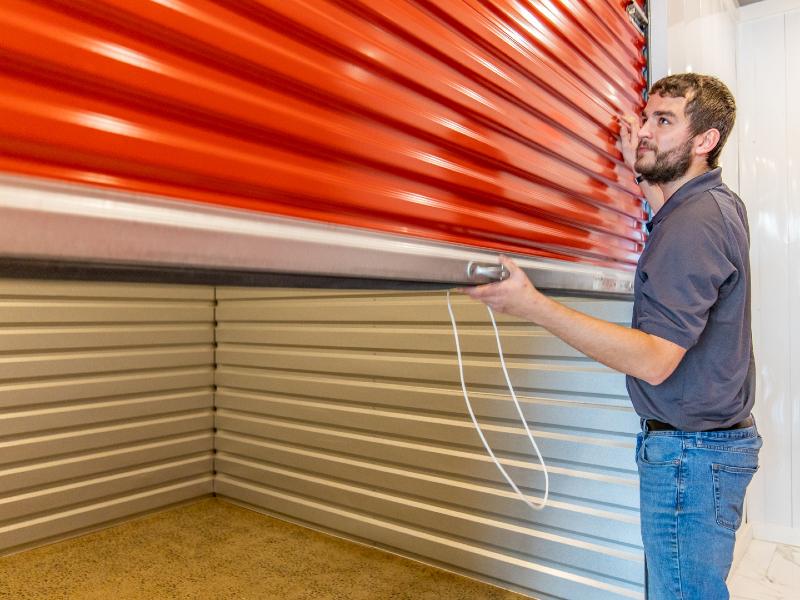 Photo of a Modern Storage employee opening a storage unit door.
