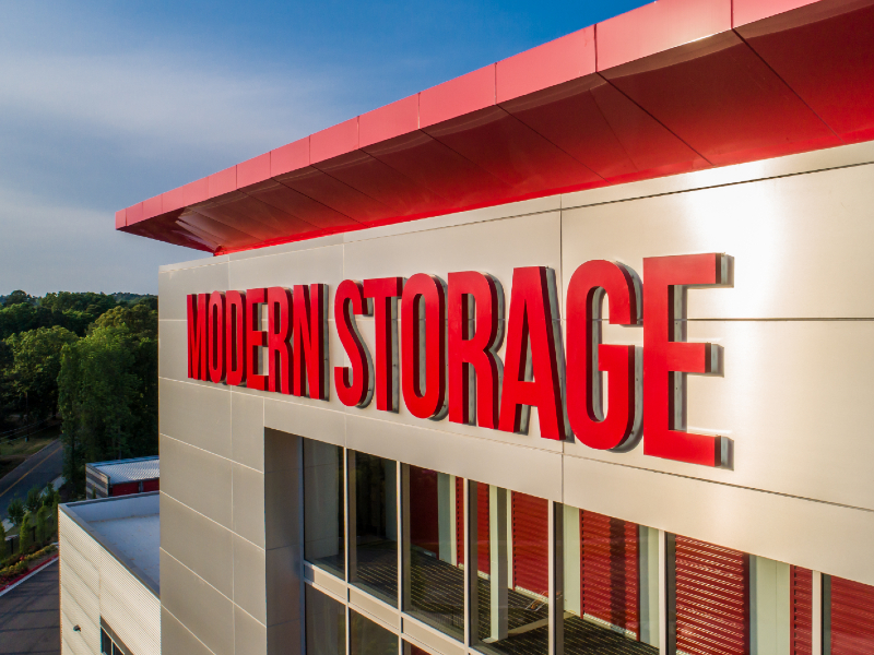 Photo of Modern Storage facility with location sign. Keep reading to learn more about our amazing storage amenities.