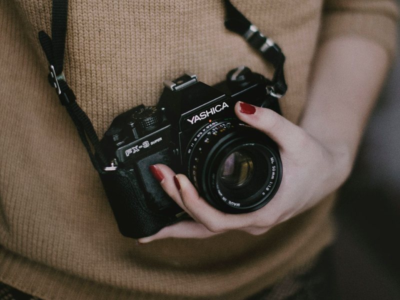 Photo of woman holding camera. If one of your hobbies is photography, rent a storage unit from Modern Storage to safely storage and organize your equipment!