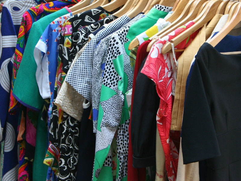 Photo of clothes hanging on a rack. Learn how to store clothes in a storage unit with tips from the experts at Modern Storage!