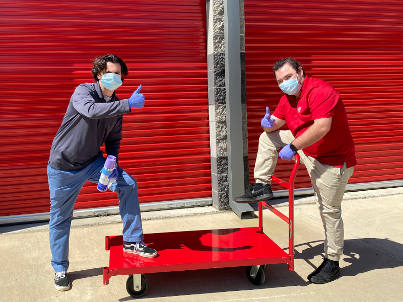 Photo of Modern Storage staff members wearing masks, pushing a moving cart, and having fun. Moving day can be more fun when you rent a storage unit at Modern Storage!