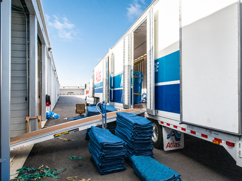 Photo of an 18-wheeler parked in front of a storage unit at Modern Storage. Palettes are being unloaded from the truck.