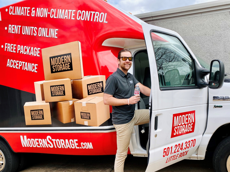 Photo of a man wearing sunglasses and holding a water bottle next to a free moving truck at a Modern Storage facility.