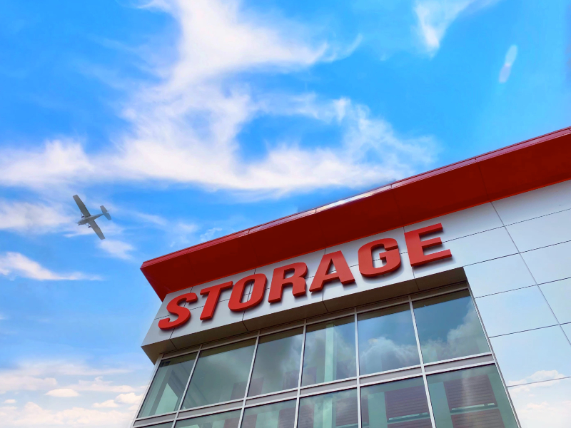 Photo of an airplane flying over a Modern Storage facility through a clear, blue summer sky.