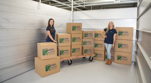 STORExpress Self Storage Customer Service Reps With Moving Boxes And Carts